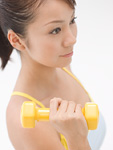 ダンベル体操をする若い女性