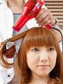 髪をブローされる若い女性