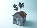 円とドルの記号と家の模型