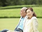 芝生に座るシニア夫婦