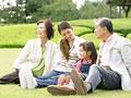 芝生に座る三世代家族