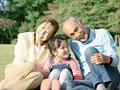芝生に座る祖父母と孫