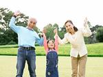 芝生で遊ぶ祖父母と孫