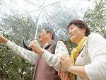 傘をさすシニア夫婦