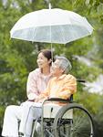 傘をさす車椅子のシニア夫婦