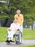 散歩をする車椅子のシニア夫婦