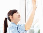 窓を拭く若い女性