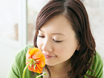 花の匂いを嗅ぐ若い女性