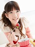 チョコレートフォンデュを食べる若い女性