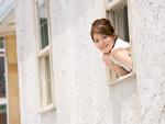 窓から顔を出す若い女性