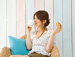 マグカップとパンを持つ若い女性