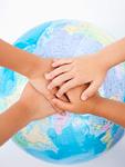 重ねた手と地球儀
