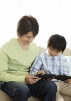 タブレットPCを操作する父と息子