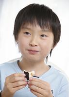 巻き寿司を食べる少年