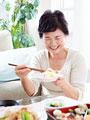 お寿司を食べるシニア女性