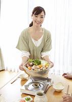 水炊き鍋を持つ若い女性
