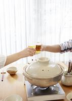ビールで乾杯する夫婦の手