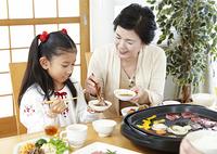 焼き肉を食べる祖母と孫
