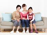 ソファーに座る三世代家族