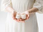 ベビーシューズを持つ妊婦