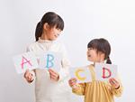 アルファベットのカードを持つ姉妹