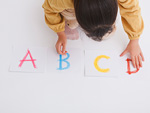 アルファベットのカードを並べる少女