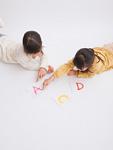 アルファベットのカードを指さす姉妹