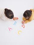 アルファベットのカードを眺める姉妹