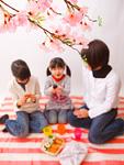 桜の下でピクニックをする母と娘
