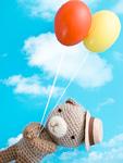風船を持つ編みぐるみのクマ