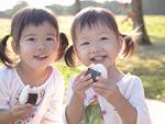 公園でおにぎりを食べる2人の女の子