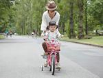 補助輪付きの自転車に乗る女の子