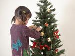クリスマスツリーの飾りつけをする女の子