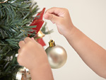 クリスマスツリーの飾りつけをする女の子の手