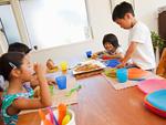 ダイニングテーブルで食事をする子供たち