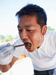 バーベキューのしいたけをつまみ食いする男性