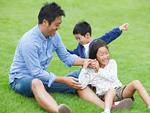 芝生の上で遊ぶ父子
