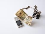 ヘルピングハンズにつままれた紙幣と携帯電話
