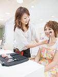 若い女性にメイクをする美容師