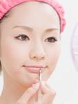 口紅を塗る若い女性