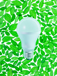 葉に囲まれたLED電球(エコロジーイメージ)