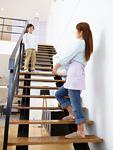 洗濯かごを持って階段をのぼる母子