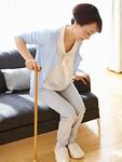 杖をついてソファから立ち上がるシニアの女性