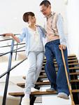 階段を下りるシニアの夫婦
