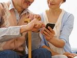 ソファに座ってスマートフォンを操作するシニアの夫婦