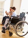 ソファに座ってスマートフォンを操作するシニアの夫婦と車椅子