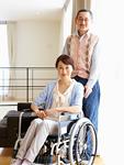 車椅子の妻のそばに立つシニアの男性