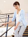 階段で膝を押さえるシニアの女性