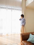 リビングルームの窓際で通話するミドルの男性