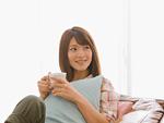 ソファに座ってコーヒーを飲む女性